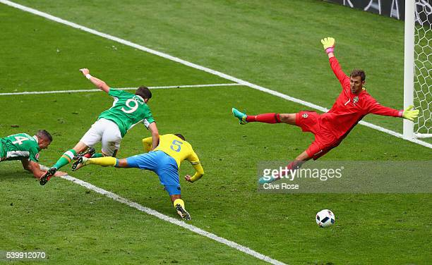 Shane Long of Republic of Ireland and Martin Olsson of Sweden dive for the ball as Andreas Isaksson of Sweden looks on during the UEFA EURO 2016...