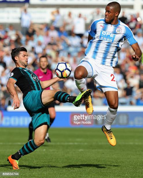 Shane Long of Southampton and Collin Quaner of Huddersfield Town battle for possession during the Premier League match between Huddersfield Town and...