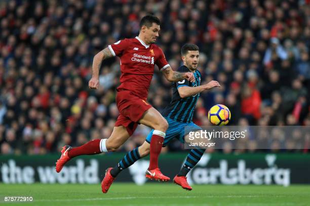 Shane Long of Southampton and Dejan Lovren of Liverpool compete for the ball during the Premier League match between Liverpool and Southampton at...