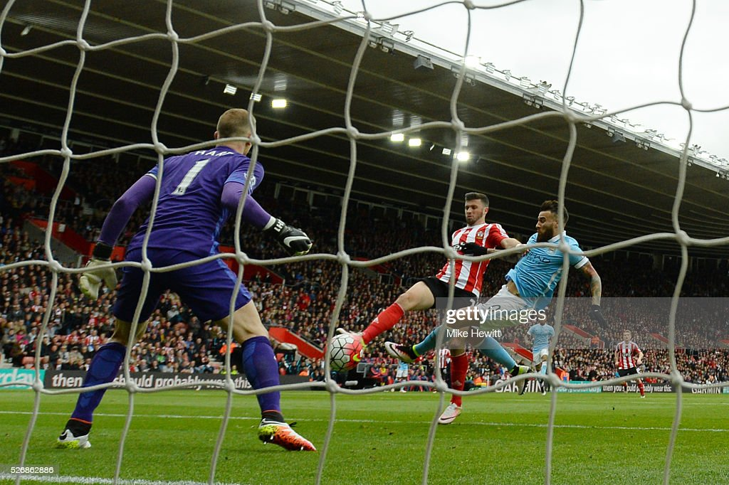Shane Long of Southampton beats Nicolas Otamendi and Joe Hart of Manchester City as he scores the opening goal during the Barclays Premier League match between Southampton and Manchester City at St Mary's Stadium on May 1, 2016 in Southampton, England.