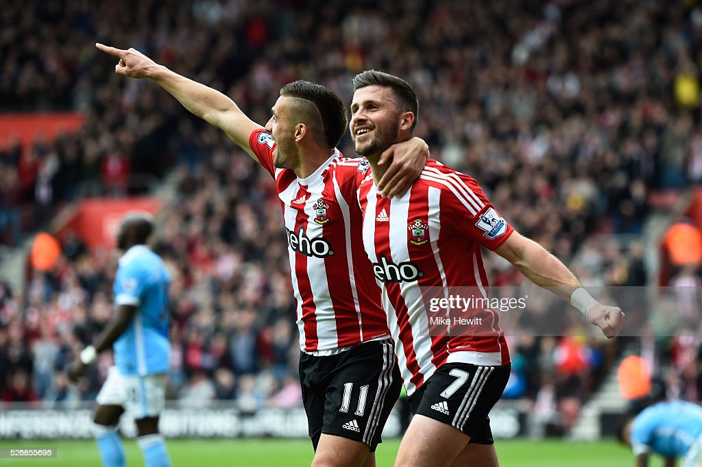 Shane Long (R) of Southampton celebrates scoring the opening goal with Dusan Tadic during the Barclays Premier League match between Southampton and Manchester City at St Mary's Stadium on May 1, 2016 in Southampton, England.
