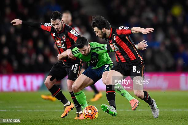 Shane Long of Southampton competes for the ball against Adam Smith and Harry Arter of Bournemouth during the Barclays Premier League match between...