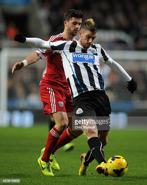 Shane Long of West Bromwich Albion competes with Davide Santon of Newcastle United during the Barclays Premier League match between Newcastle United...