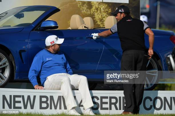 Shane Lowry of Ireland and Pablo Larrazabal of Spain takes a break on the 17th tee and check out the BMW stand during the Nordea Masters at the PGA...