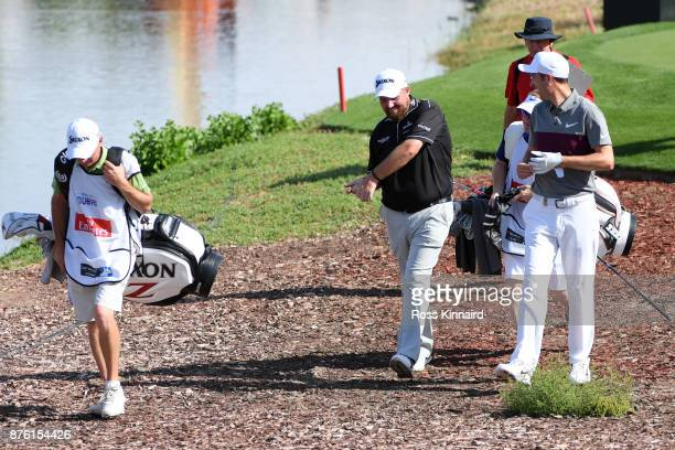 Shane Lowry of Ireland and Ross Fisher of England walk down the 18th hole during the final round of the DP World Tour Championship at Jumeirah Golf...