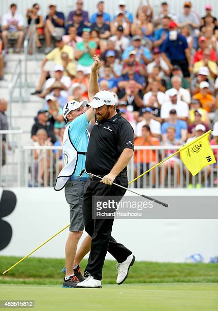 Shane Lowry of Ireland celebrates with his caddie Dermot Byrne after a birdie putt on the 18th green during the final round of the World Golf...