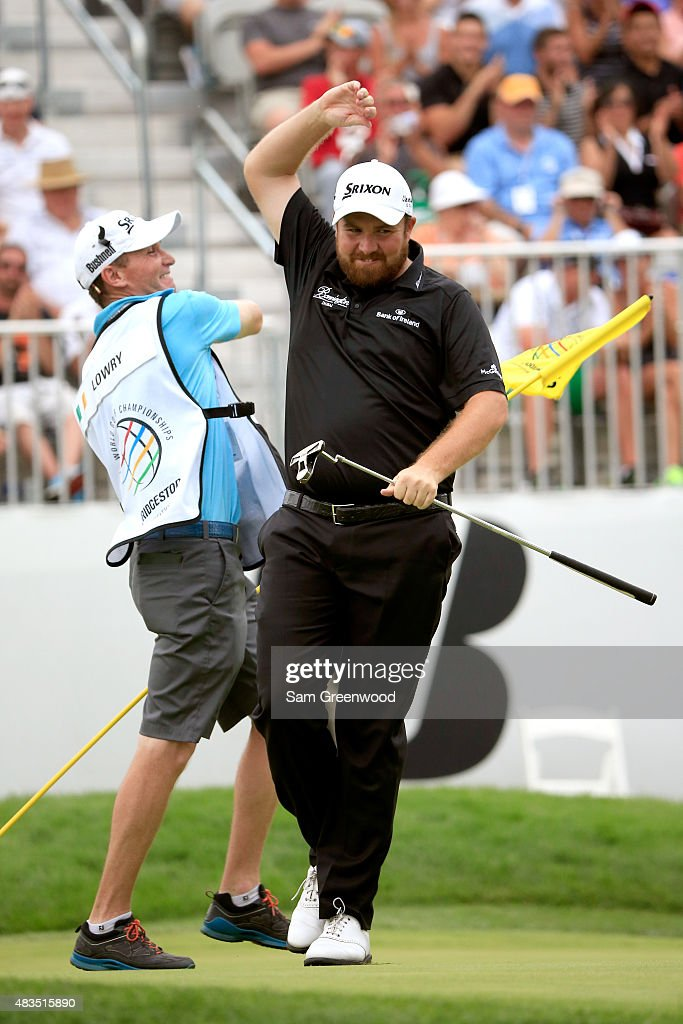 Shane Lowry of Ireland (R) celebrates with his caddie Dermot Byrne after a birdie putt on the 18th green during the final round of the World Golf Championships - Bridgestone Invitational at Firestone Country Club South Course on August 9, 2015 in Akron, Ohio.
