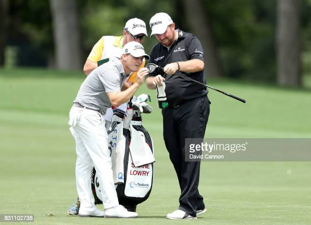 Shane Lowry of Ireland examines his broken 3 wood with his playing partner Bud Cauley of the United States before he plays his second shot on the par...