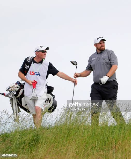 Shane Lowry of Ireland hands his club to caddie Dermot Byrne after playing his shot from the fifth tee during the second round of the 2017 US Open at...