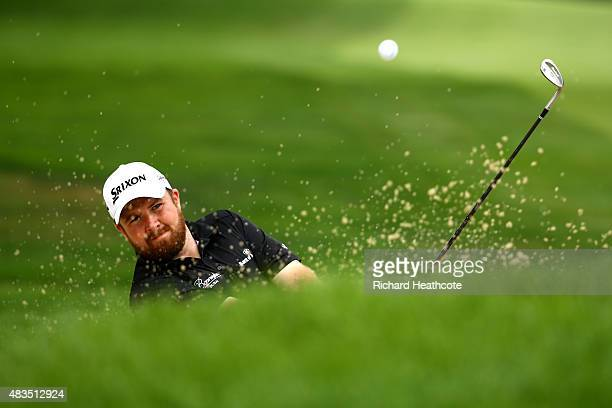 Shane Lowry of Ireland hits out of a bunker near the 11th green during the final round of the World Golf Championships Bridgestone Invitational at...