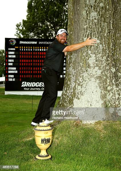 Shane Lowry of Ireland hugs a tree near the 18th green with the Gary Player Cup after winning the World Golf Championships Bridgestone Invitational...