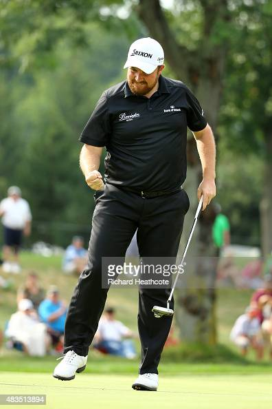 Shane Lowry of Ireland reacts after a par putt on the 14th green during the final round of the World Golf Championships Bridgestone Invitational at...