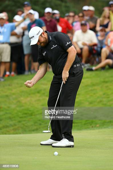 Shane Lowry of Ireland reacts to a par putt on the 17th green during the final round of the World Golf Championships Bridgestone Invitational at...