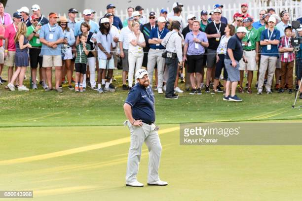 Shane Lowry of Ireland reacts to his putt on the 18th hole green as fans watch during round one of the World Golf Championships Dell Technologies...