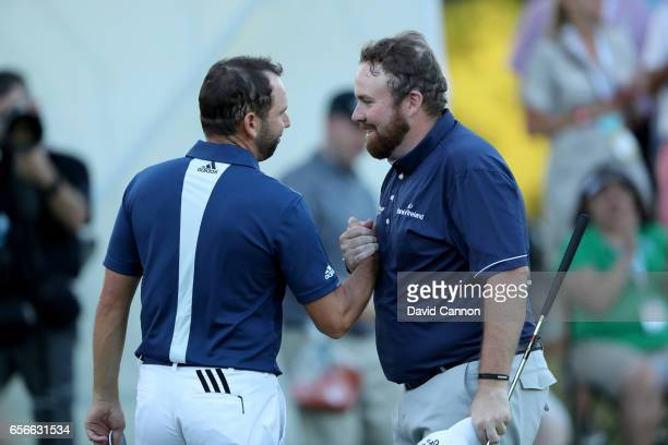 Shane Lowry of Ireland shakes hands with his opponent Sergio Garcia of Spain on the par 4 18th hole after they had halved their match during the...