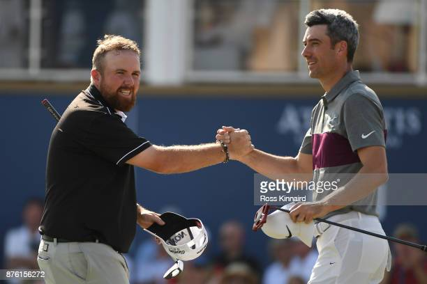 Shane Lowry of Ireland shakes hands with Ross Fisher of England on the 18th green during the final round of the DP World Tour Championship at...