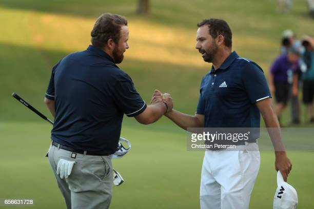 Shane Lowry of Ireland shakes hands with Sergio Garcia of Spain after they halved their match during round one of the World Golf ChampionshipsDell...