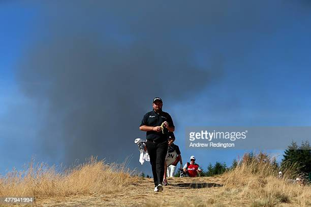 Shane Lowry of Ireland walks the 15th hole as smoke from a nearby fire is seen in the distance during the third round of the 115th US Open...