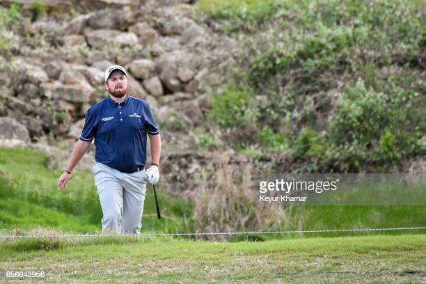 Shane Lowry of Ireland watches his shot out of a hazard off the 18th hole during round one of the World Golf Championships Dell Technologies Match...