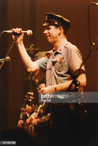 Shane MacGowan of The Pogues performs on stage dressed in NYPD cop uniform at Brixton Academy on St Patricks Day March 17th 1987 in London England