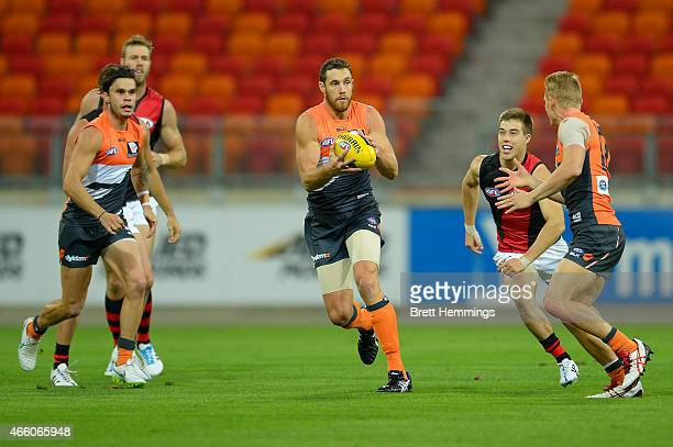 Shane Mumford of the Giants controls the ball during the NAB Challenge AFL match between the Greater Western Sydney Giants and the Essendon Bombers...