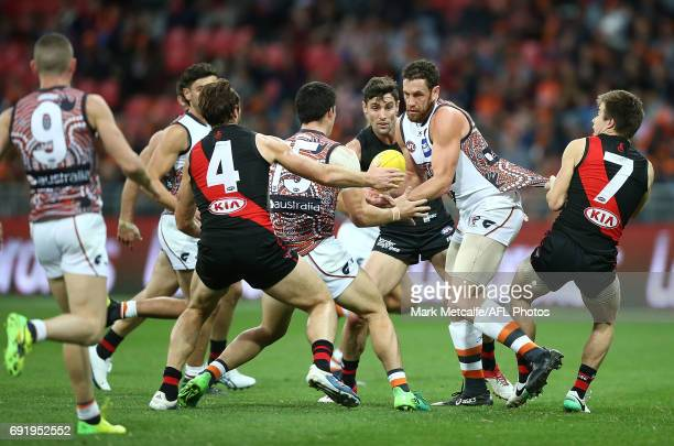 Shane Mumford of the Giants handpasses the ball during the round 11 AFL match between the Greater Western Sydney Giants and the Essendon Bombers at...