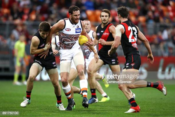Shane Mumford of the Giants is tackled during the round 11 AFL match between the Greater Western Sydney Giants and the Essendon Bombers at Spotless...
