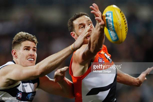 Shane Mumford of the Giants taps the ball from Zac Smith of the Cats during the round 23 AFL match between the Geelong Cats and the Greater Western...