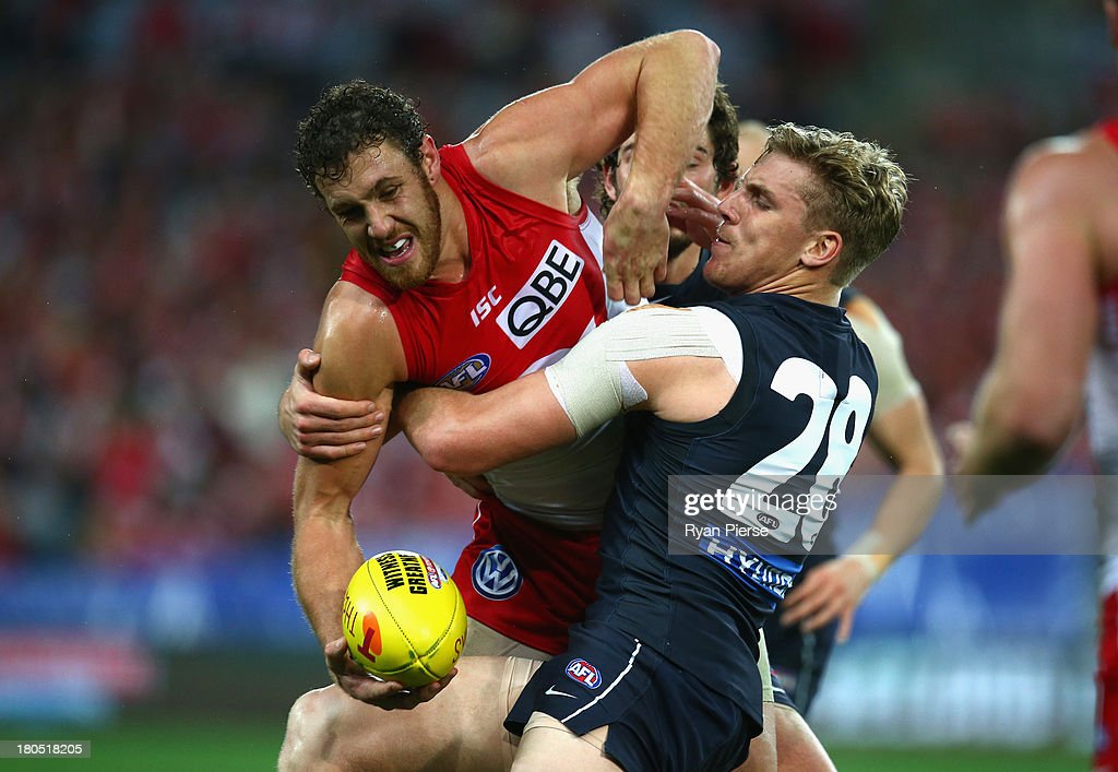 Shane Mumford of the Swans is tackled by Tom Bell of the Blues during the AFL First Semi Final match between the Sydney Swans and the Carlton Blues at ANZ Stadium on September 14, 2013 in Sydney, Australia.