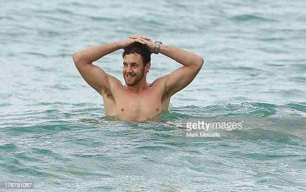 Shane Mumford wades in the ocean during a during a Sydney Swans AFL recovery session at Coogee Beach on August 19 2013 in Sydney Australia