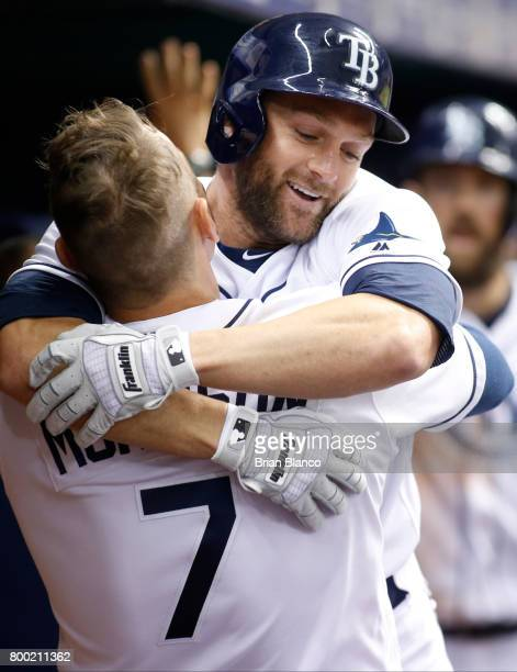 Shane Peterson of the Tampa Bay Rays celebrates hits a tworun home run in the dugout with teammate Logan Morrison during the third inning of a game...