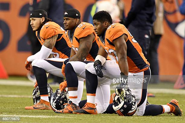 Shane Ray of the Denver Broncos Todd Davis and Corey Nelson kneel after teammate Zaire Anderson was injured against the Oakland Raiders during the...