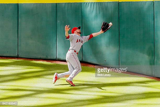 Shane Robinson of the Los Angeles Angels of Anaheim has the ball go off the tip of his glove on a deep fly ball by Marwin Gonzalez of the Houston...