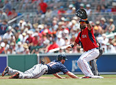 Shane Robinson of the Minnesota Twins dives back to first base safe ahead of the tag by Mike Napoli of the Boston Red Sox during a spring training...