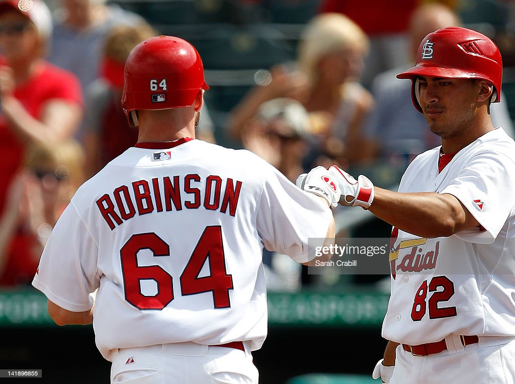 Shane Robinson #64 of the St. Louis Cardinals celebrates with Erik Komatsu #82 after scoring during a game against the Minnesota Twins at Roger Dean Stadium on March 25, 2012 in Jupiter, Florida. The St. Louis Cardinals defeated the Minnesota Twins 9-2.