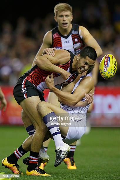 Shane Savage of the Saints gets a handball out while being tackled during the round 10 AFL match between the St Kilda Saints and the Fremantle...