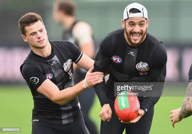 Shane Savage of the Saints handballs whilst being tackled Jack Sinclair during a St Kilda Saints AFL training session at Linen House Oval on May 30...