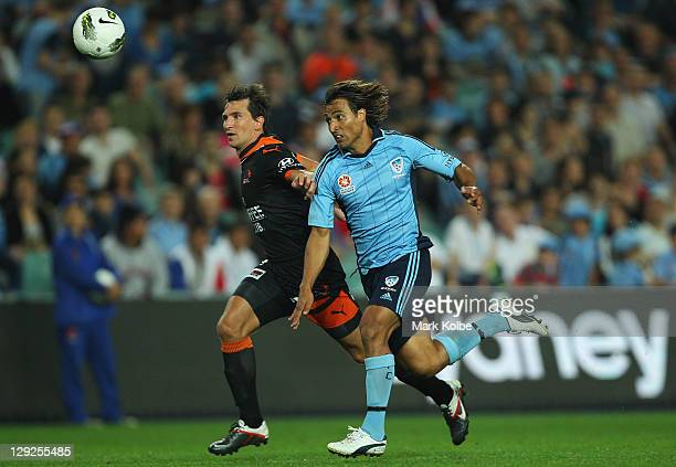 Shane Stefanutto of the Roar and Nick Carle of Sydney FC race for the ball during the round two ALeague match between Sydney FC and the Brisbane Roar...