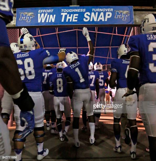 Shane Tucker of the Middle Tennessee State University Blue Raiders hits a sign saying 'Win the Snap' as he reenters the field from half time of an...