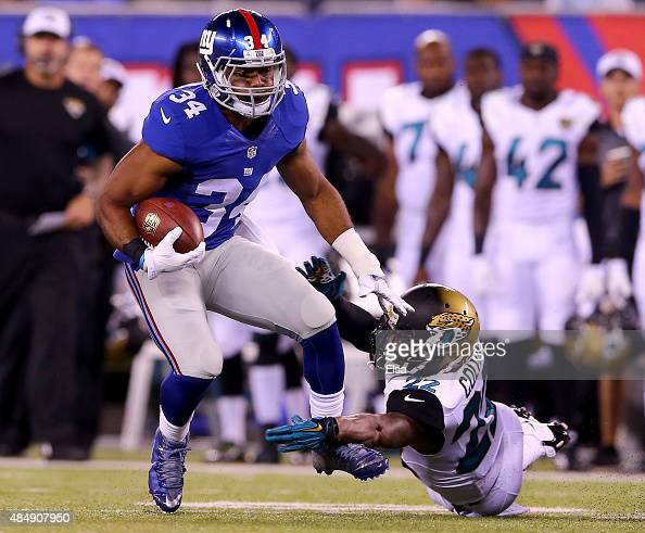 Shane Vereen of the New York Giants carries the ball as Aaron Colvin of the Jacksonville Jaguars defends at MetLife Stadium on August 22 2015 in East...