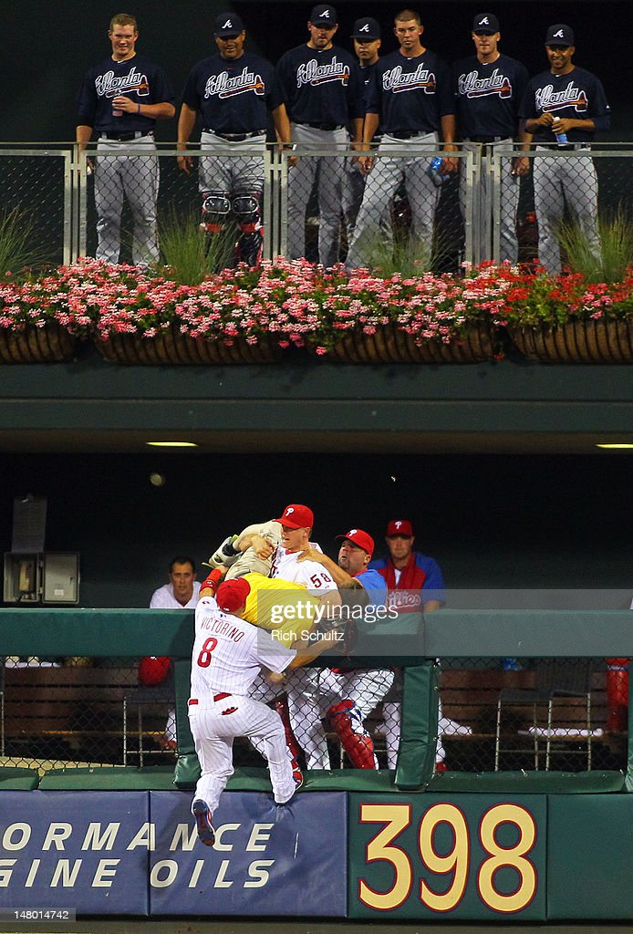 Shane Victorino #8 and closer <a gi-track='captionPersonalityLinkClicked' href=/galleries/search?phrase=Jonathan+Papelbon&family=editorial&specificpeople=453535 ng-click='$event.stopPropagation()'>Jonathan Papelbon</a> #58 of the Philadelphia Phillies wrestle with a fan who jumped into the bullpen after running on the field in the seventh inning during a MLB baseball game against the Atlanta Braves on July 7, 2012 at Citizens Bank Park in Philadelphia, Pennsylvania.