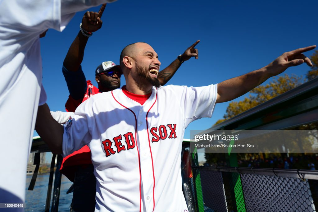 Shane Victorino #18 and David Ortiz #34 of the Boston Red Sox react to the crowd on the banks of the Charles during the river portion of a victory parade on November 2, 2013 through Boston, Massachusetts.
