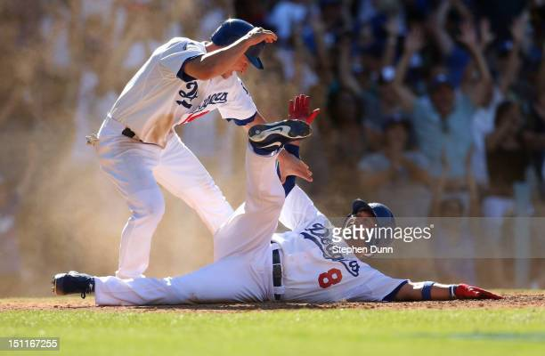 Shane Victorino and Mark Ellis of the Los Angeles Dodgers celebrate after both score on a two run walk off double by Adrian Gonzalez in the ninth...
