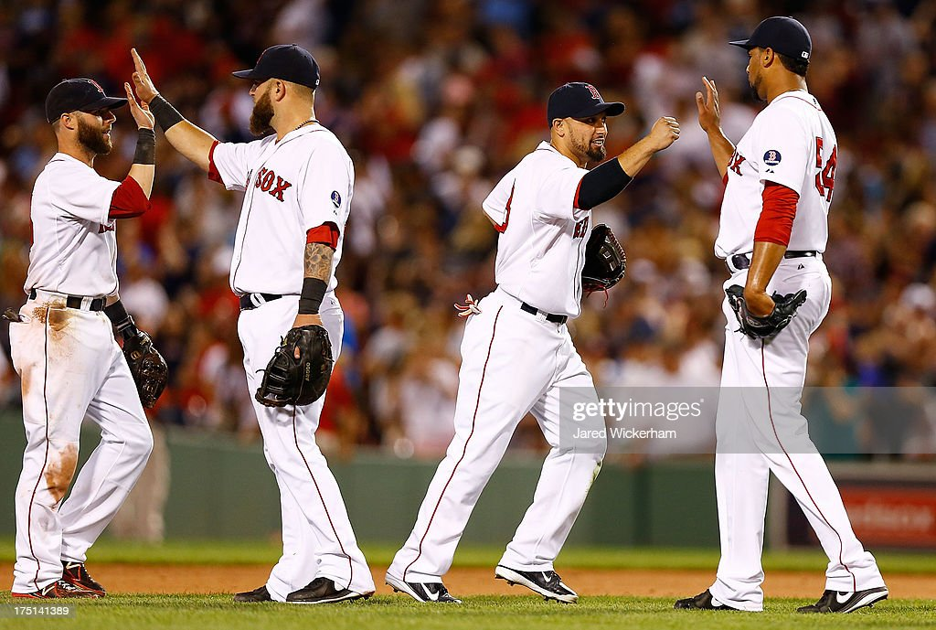 Shane Victorino of the Boston Red Sox congratulates Pedro Beato of the Boston Red Sox following their win against the Seattle Mariners during the...