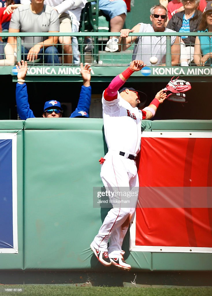 <a gi-track='captionPersonalityLinkClicked' href=/galleries/search?phrase=Shane+Victorino&family=editorial&specificpeople=576251 ng-click='$event.stopPropagation()'>Shane Victorino</a> #18 of the Boston Red Sox hits the wall and loses his glove as the ball hit by Emilio Bonifacio #1 of the Toronto Blue Jays goes over the right field wall for a home run in front of the Toronto Blue Jays bullpen in the fourth inning during the game on May 12, 2013 at Fenway Park in Boston, Massachusetts. Victorino would be shaken up on the play but would return to the game.