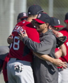 Shane Victorino of the Boston Red Sox hugs Grady Sizemore during a Spring Training workout at Fenway South on February 18 2014 in Fort Myers Florida