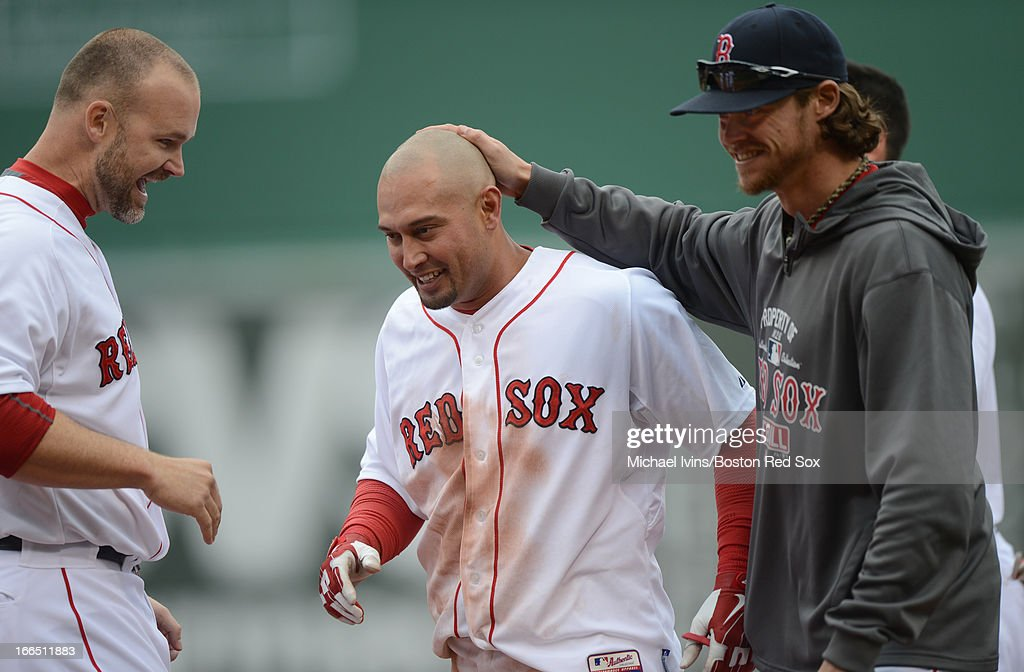 <a gi-track='captionPersonalityLinkClicked' href=/galleries/search?phrase=Shane+Victorino&family=editorial&specificpeople=576251 ng-click='$event.stopPropagation()'>Shane Victorino</a> #18 of the Boston Red Sox is congratulated by teammates David Ross #3, left, and Clay Buchholz #11 after hitting a game winning single against the Tampa Bay Rays in the tenth inning on April 13, 2013 at Fenway Park in Boston, Massachusetts.