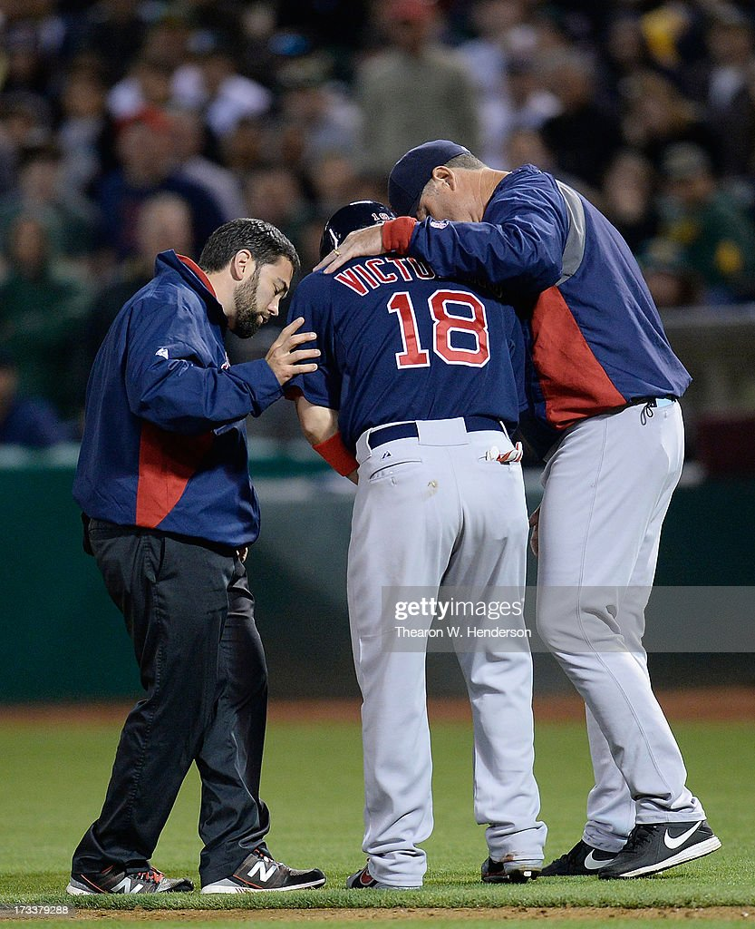 Shane Victorino #18 of the Boston Red Sox is tended to by manager John Farrell (R) and a member of the training staff after getting hit on the hand with a pitch in the eighth inning against the Oakland Athletics at O.co Coliseum on July 12, 2013 in Oakland, California.