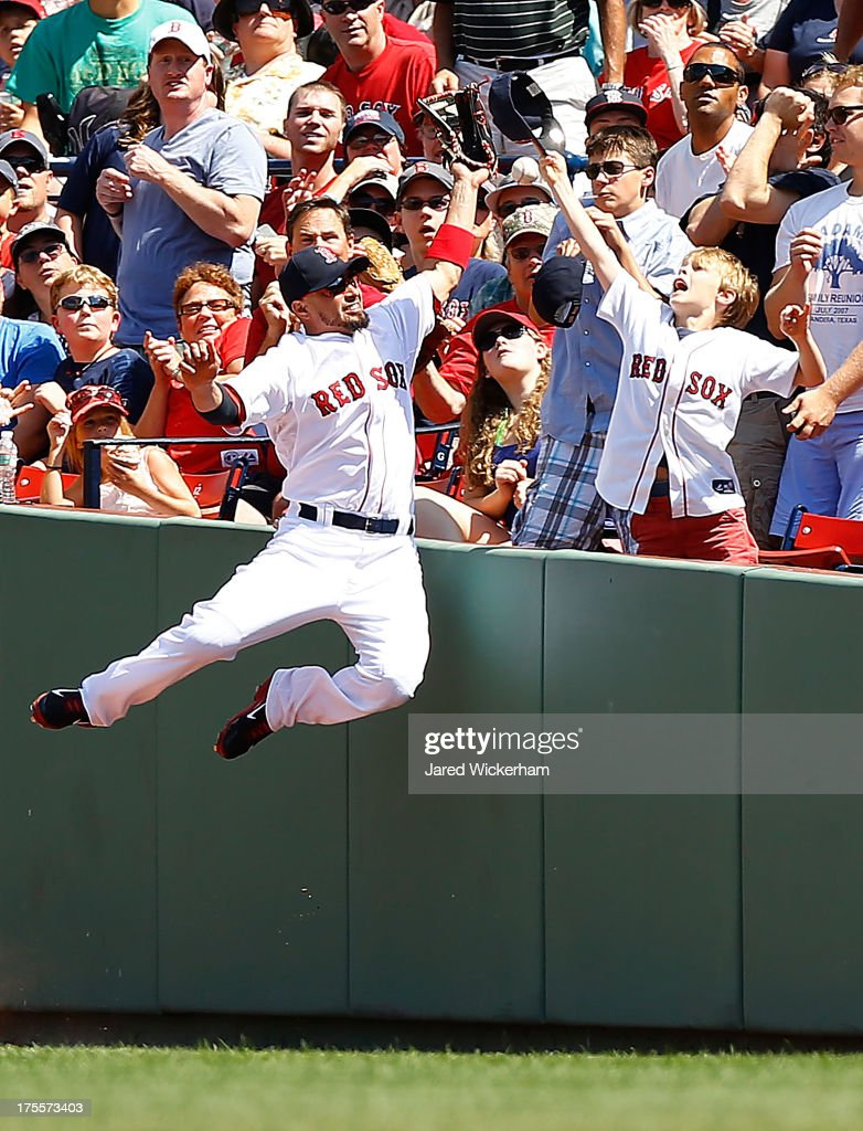 Shane Victorino #18 of the Boston Red Sox leaps over the right field wall in foul territory while missing a pop fly in front of a young fan during the game against the Arizona Diamondbacks on August 4, 2013 at Fenway Park in Boston, Massachusetts.