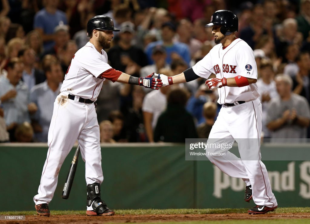 Shane Victorino #18 of the Boston Red Sox, right, is congratulated by teammate Dustin Pedroia #15 of the Boston Red Sox after his home run against the Baltimore Orioles during the sixth inning of the game at Fenway Park on August 29, 2013 in Boston, Massachusetts.